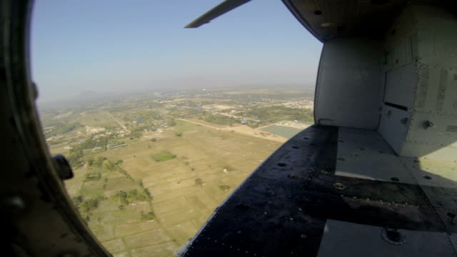 aerial view tropical sky and ground from helicopter passenger cabin in flight video