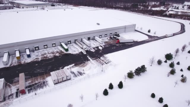 Aerial warehouse parking lot covered in snow video