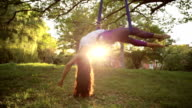 Aerial yoga practitioner stretches herself while suspended on hammock. video