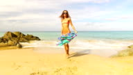 Aerial: Young lady dancing on the beach. video