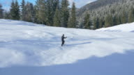 Aerial - Young man winter hiking in a company of his dog video