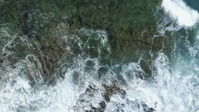 Aerial Zoom Out Shot Of Waves Washing Up On Rock video