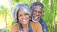 Affectionate African American senior couple smiling looking to camera video