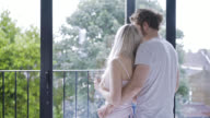 Affectionate couple embracing looking out the window video
