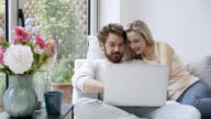 Affectionate couple looking at photos on their laptop video