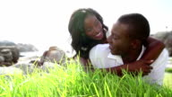 Affectionate couple lying on grass smiling video
