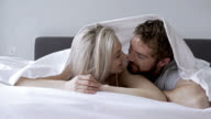 Affectionate couple lying on their tummies in bed kissing video