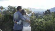 Affectionate couple pointing towards the mountains and looking the view video
