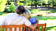 Affectionate couple sitting on park bench video