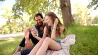 Affectionate couple smiling at something on a phone video