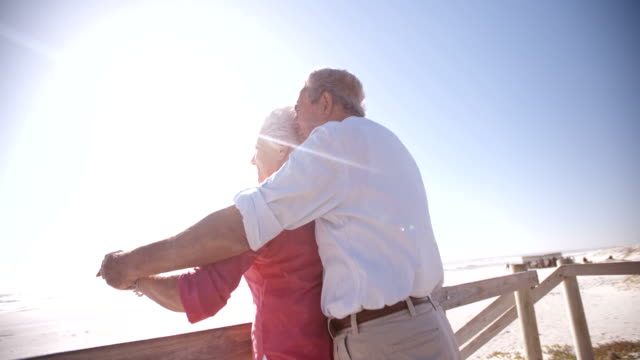 Affectionate elderly retired couple enjoying time at the beach video