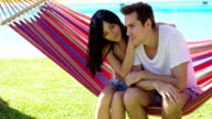 Affectionate young couple sitting on a hammock video