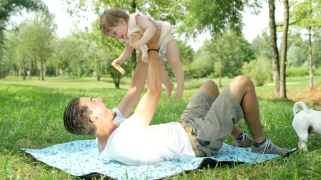 SLOW MOTION: Affectionate young father playing with baby daughter in local park video