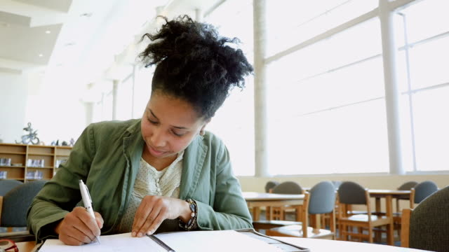 African American adult college student studying in brightly lit library video
