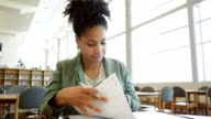 African American adult woman writing while studying in college library video