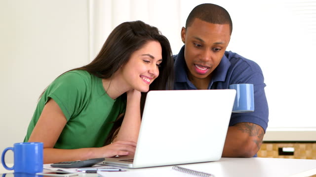 African american and caucasian couple paying bills together video