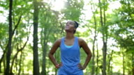 African American athletic woman checking pulse while off road running video