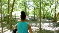 African American athletic woman is running off road in park video
