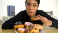 African American business woman eating a pile of donuts video