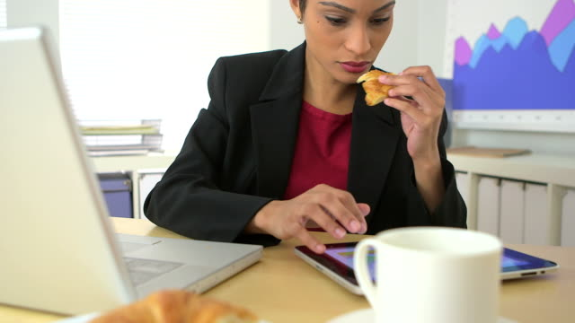 African American business woman eating croissant and using tablet computer video