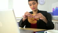 African American business woman eating croissant at desk video