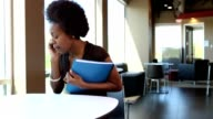 African American Business Woman on phone sits down to work video