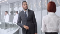 DS African American businessman meeting with woman in corporate hallway video