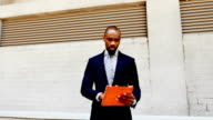 African American businessman stand with tablet outdoors video