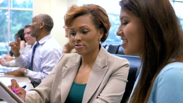 African American businesswoman taking notes while attending business conference with colleague video