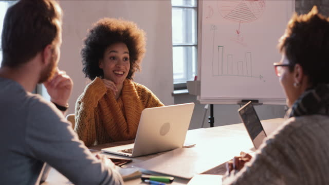 African American businesswoman using laptop and communicating with colleagues on a meeting. video
