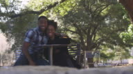 African American couple at an outdoor table smiling for the camera, then laughing and talking, bokeh video