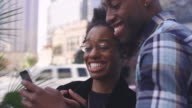 African American couple in a city taking pictures together with a cell phone, close up video