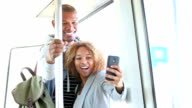 African American couple riding train, taking selfie on mobile phone video