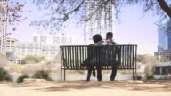 African American couple sitting together on a bench on the city waterfront video