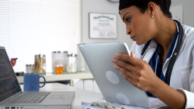 African American doctor talking on smartphone and looking at devices video