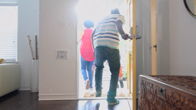 African American family leaving the house with front door open video