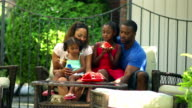 African American family outdoors on a couch together video