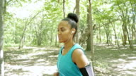 African American female runner running off road in wooded park video