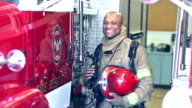 African American fireman standing by truck at station video