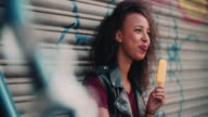 African American girl smiling while enjoying an orange ice lolly video