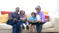 African American grandparents with grandchildren on sofa, reading video