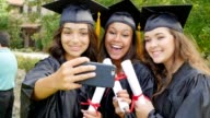 African American, Hispanic and Caucasian college friends take selfies after graduation video