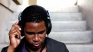 African American listening to Headphones on steps video