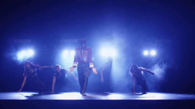 African american male in a hat and costume is leading a group of dancers while singing on a dark stage with lights. video