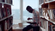African american man with books at window video