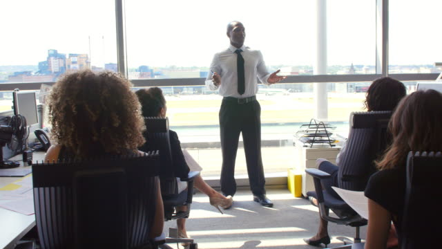 African American manager speaking to coworkers in office video