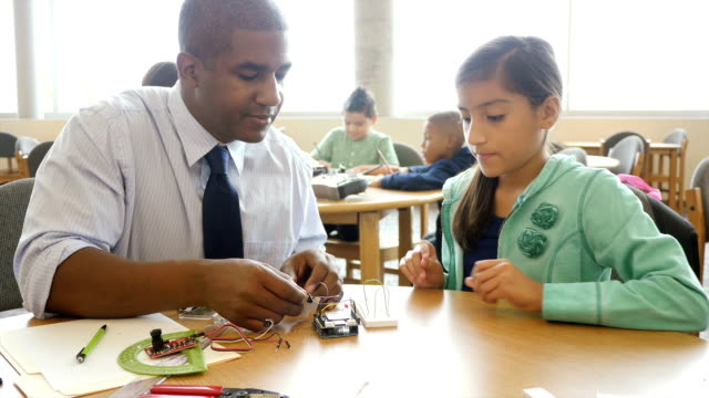 African American mid-adult teacher helps pre-teen student with electrical components video