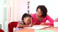 African American mother helping her daughter to do homework video