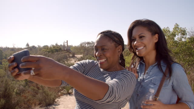 African American mum and her adult daughter taking a selfie video