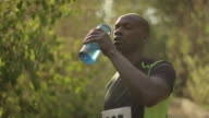 African American runner drinking water and recovering from race video